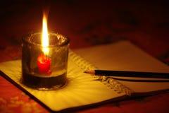 Lápiz puesto en el cuaderno con la luz de la vela Foto de archivo libre de regalías