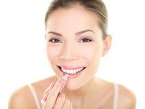 Läppstiftmakeupkvinna som sätter skönhet för omsorg för kantbalsam Arkivbild