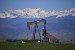 Ölquelle und Schnee mit einer Kappe bedeckte Spitzen Lizenzfreies Stockfoto