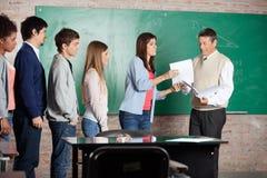 Lärare Giving Test Result till studenten At Classroom Arkivfoto