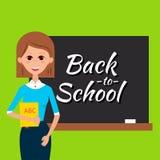 Lärare med boken och tillbaka till skolasvart tavla Royaltyfria Foton