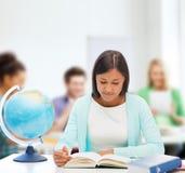Lärare med jordklotet och boken på skolan Royaltyfri Foto