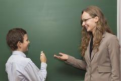 Lärare och student på brädet Arkivbild