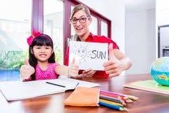 Lärare som ger språkkurser till det kinesiska barnet Arkivbild