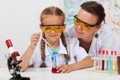 Lärare som har uppsikt över kemiskt experiment i vetenskapsgrupp Fotografering för Bildbyråer