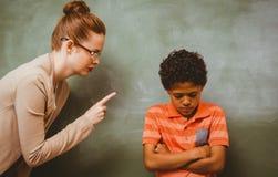 Lärare som ropar på pojken i klassrum Arkivbild