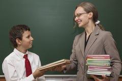 Lärarehänder över en bok till studenten Royaltyfria Bilder