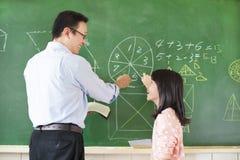 Läraren undervisar studenten att lösa matematikfrågorna Arkivbild