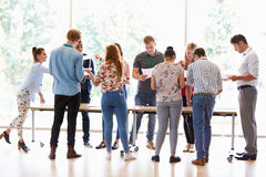 LärareWith College Students anseende vid skrivbord i klassrum Royaltyfri Bild