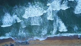 Aerial of the sandy beach that is washed by turquoise sea waves in Sri Lanka. Lright turquoise sea waves foam and waves break on the sandy shore at the resort in stock video