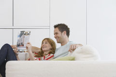 Läs- broschyr för gladlynta och avkopplade par på soffan Royaltyfri Foto