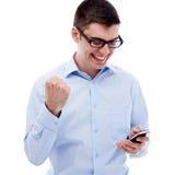 Läs- goda nyheter för upphetsad grabb vid smartphonen Royaltyfri Bild