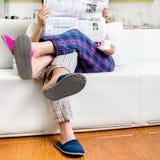 Läs- tidning för gift par iklädd pyjamas som sitter i s Arkivbild
