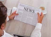Läs- tidning för man med kaffe på skrivbordet Arkivfoto