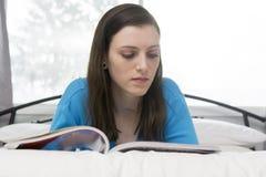 Läs- tidskrift för tonårs- flicka på säng Arkivfoton