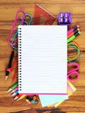 Löschen Sie gezeichnetes Notizbuch mit zugrunde liegendem Schulbedarfrahmen auf Holz Lizenzfreies Stockbild