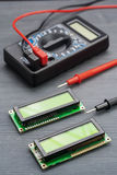 LSD screen wh1602 and multimeter on wooden background.  Stock Photos
