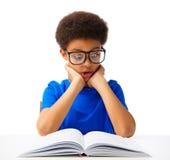 Läsebok för skolapojke med överraskning Arkivbild