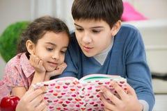 Läsebok för två barn hemma Fotografering för Bildbyråer