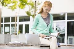 Läsebok för ung kvinna på högskolauniversitetsområdet Arkivfoto