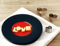 Älska ordet, ljusbruna kakabokstäver på det målade krukmakeritefatet med den hjärta formade kakaskäraren Royaltyfri Fotografi