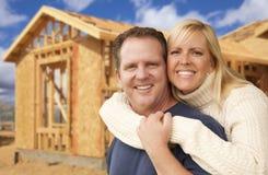 Älska par framme av ny hem- konstruktion som inramar platsen Arkivbild