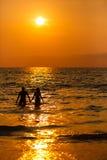 Älska par på solnedgången i havet Arkivbilder