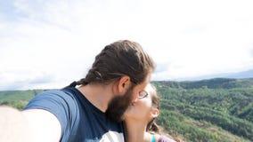 ?lska par som tar en selfie, medan kyssa i utomhus- Pojkv?n med ett sk?gg Familj som tillsammans reser royaltyfri foto