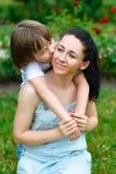 Älska sonen som in kramar och kysser hans lyckliga moder Royaltyfria Bilder