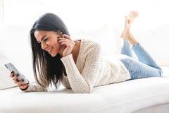 ?lskv?rd ung kvinna som hemma kopplar av p? en soffa arkivbild