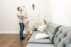 ?lskv?rda unga par i en vardagsrum med en modern inre framsida - - framsida arkivfoto