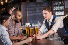 Älskvärd afton Tre vänmän som dricker öl och har gyckel t Arkivfoto