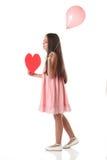 Älskvärd flicka som rymmer en röd hjärtaform och en rosa ballong Arkivbild