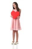 Älskvärd flicka som rymmer en röd hjärtaform, över vit bakgrund Arkivfoton