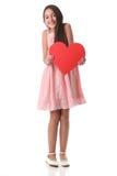 Älskvärd flicka som rymmer en röd hjärtaform, över vit bakgrund Arkivbild