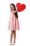 Älskvärd flicka som rymmer en röd hjärtaform, över vit bakgrund Royaltyfri Fotografi
