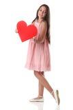 Älskvärd flicka som rymmer en röd hjärtaform, över vit bakgrund Arkivfoto