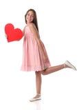Älskvärd flicka som rymmer en röd hjärtaform, över vit bakgrund Royaltyfri Foto