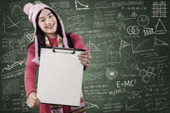 Älskvärd flicka som visar den tomma skrivplattan Arkivfoto