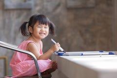 Älskvärd framsida av toothy le asiatiska barn som är practive till att skriva Royaltyfria Foton