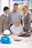 Ältere Architektenvertretungsarbeit zum Team auf Laptop Stockbild