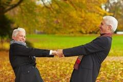 Ältere Bürger, die in einen Park tanzen Stockbild