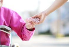 Ältere Dame in den Rollstuhl-Holding-Händen Stockfotos