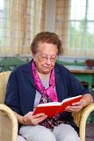 Ältere, die in einem Stuhl sitzen Lizenzfreie Stockfotos