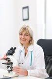 Ältere Doktorfrau, die mit Mikroskop am Labor arbeitet Stockbilder