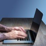 Ältere erwachsene Mannnotenarten auf Laptop Stockfoto