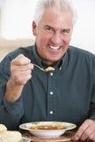 Ältere Fleisch fressende Suppe, lächelnd an der Kamera Stockbild