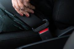 ?ltere ?ltere Frau befestigt einen Sicherheitsgurt in einem Auto, das gr?ne und gelbe Jacke tr?gt lizenzfreie stockfotos