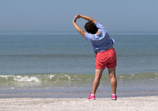 Ältere Frau, die auf einem Strand trainiert Lizenzfreies Stockfoto