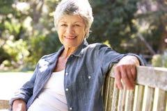 Ältere Frau, die auf Park-Bank sich entspannt Stockbild